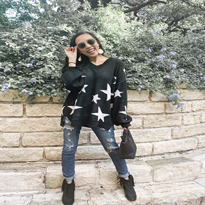 person wearing star sweater in black
