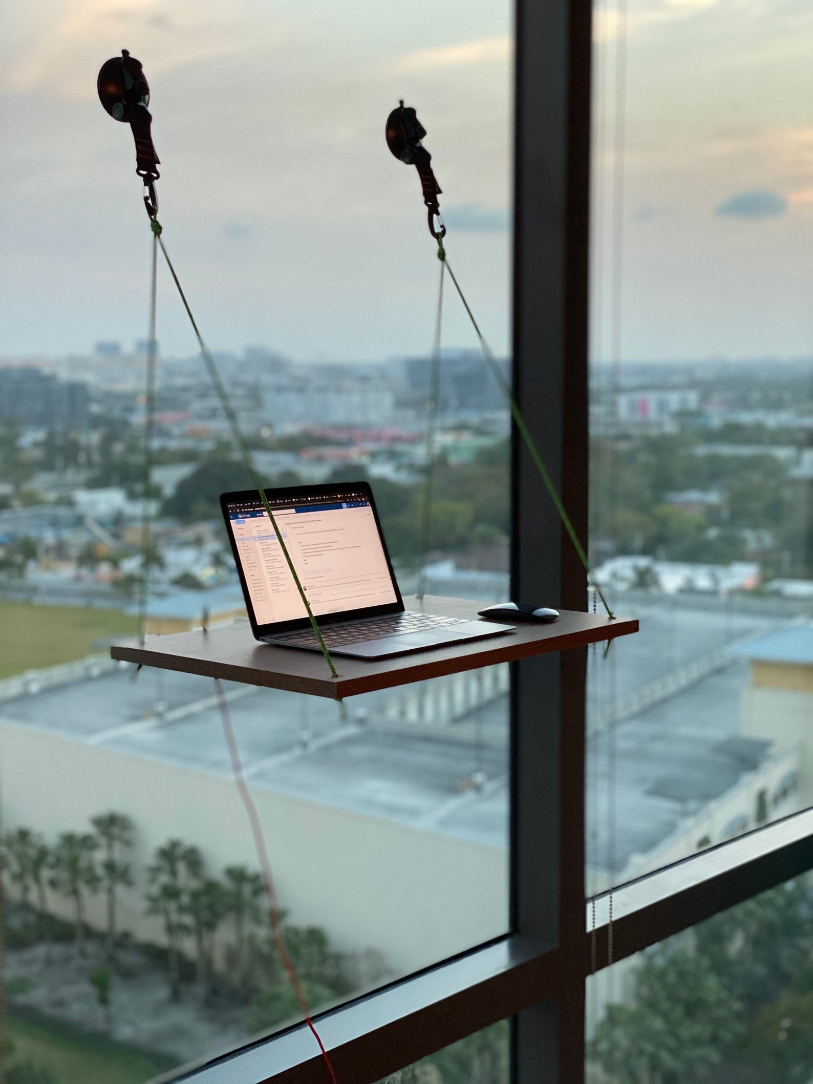 A wooden desk hung up by ropes and suction to a window with a laptop on it