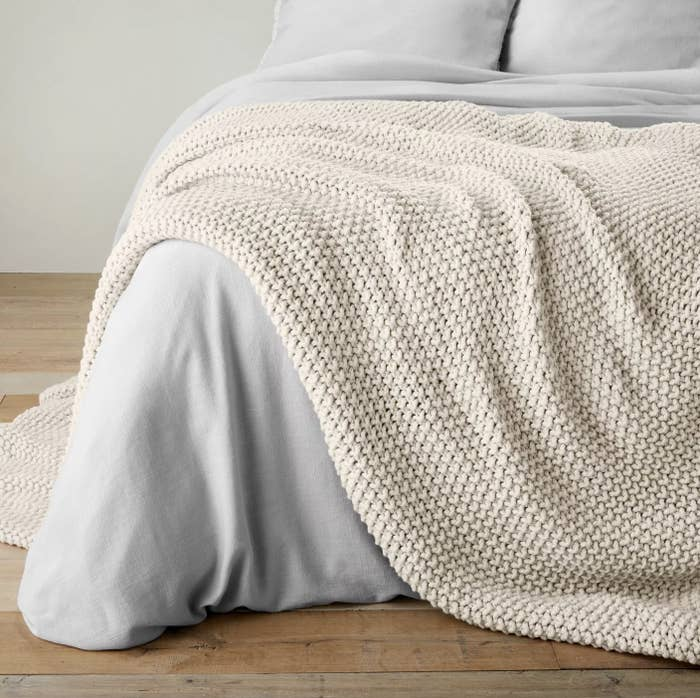 The oatmeal color knit blanket on a bed