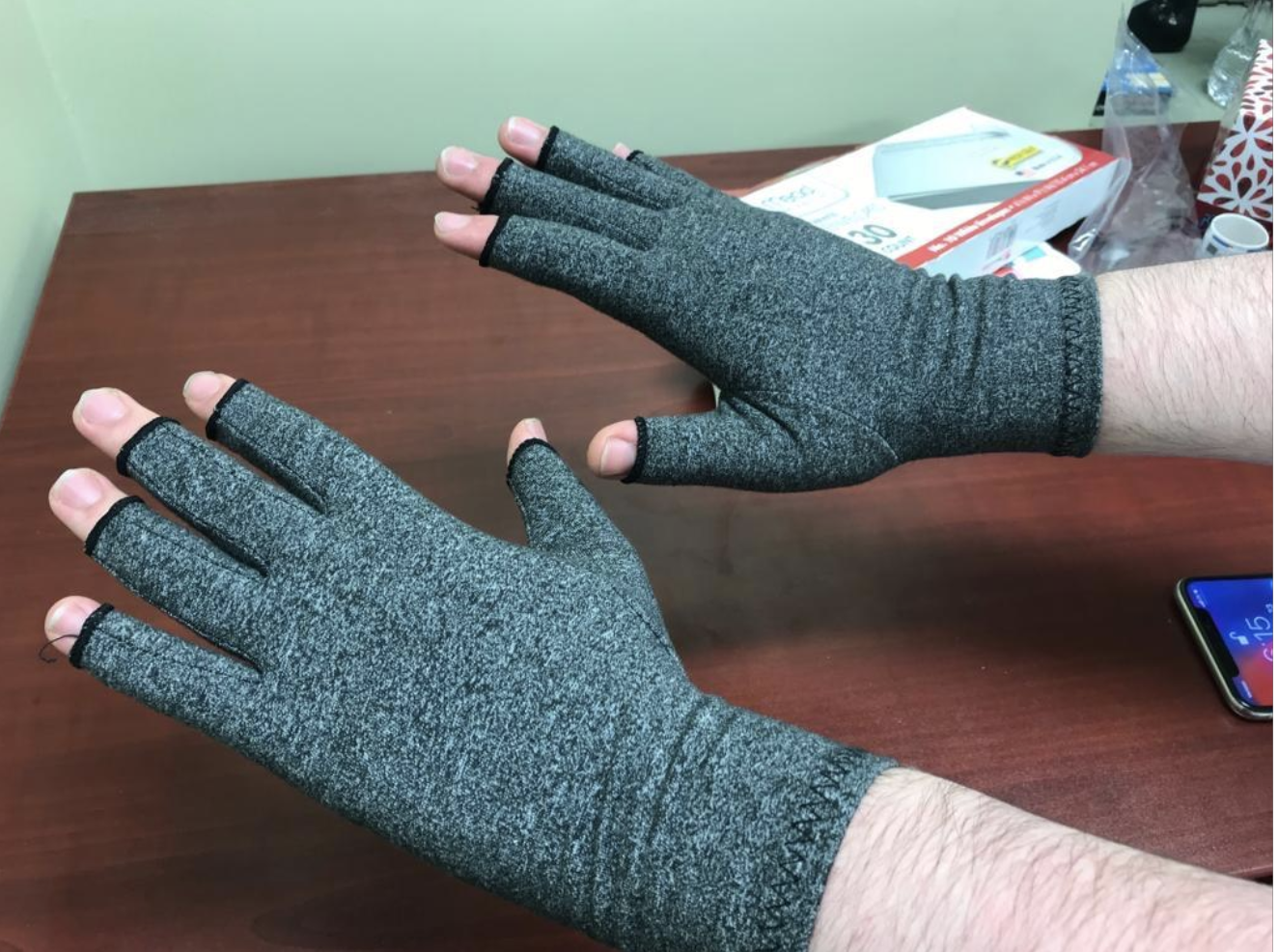 Reviewer with gray fingerless compression gloves on hands