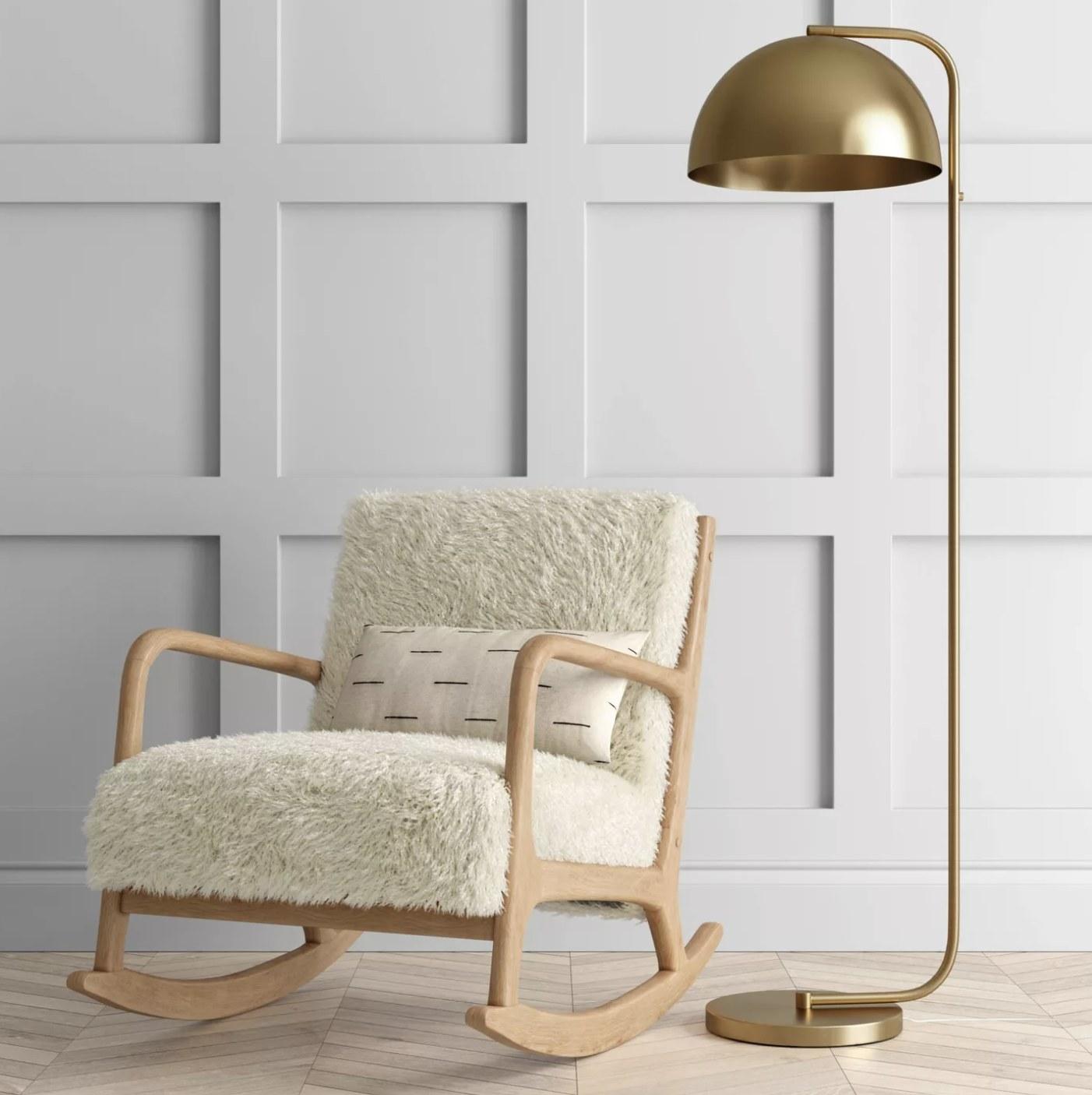 A brass floor lamp next to a chair