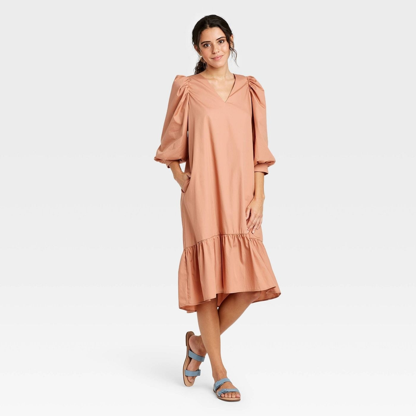 Model wearing peach dress with 3/4 length bell sleeves
