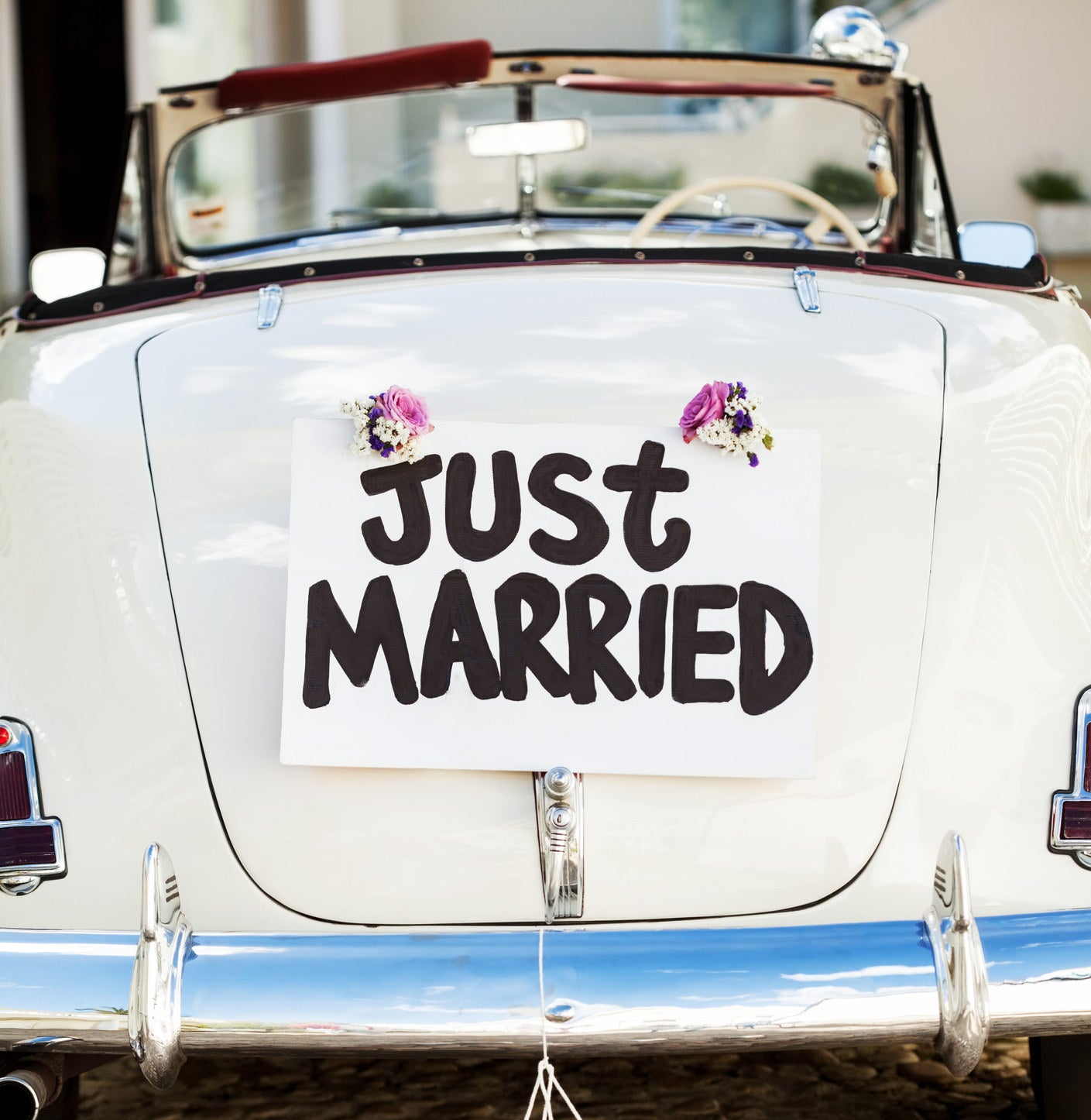 "A ""Just Married"" sign and cans attached to convertible car's trunk."