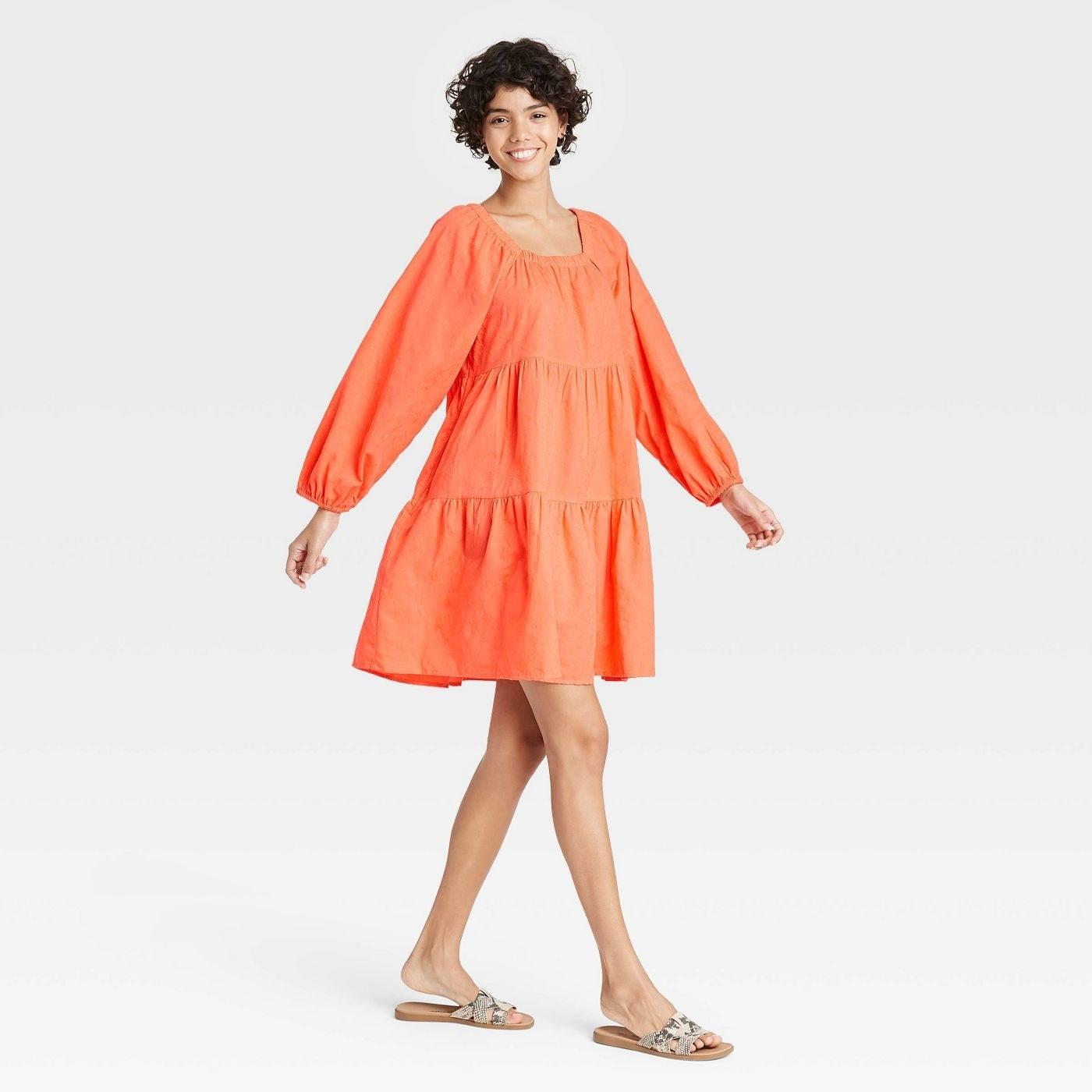 Model wearing  long sleeve orange dress