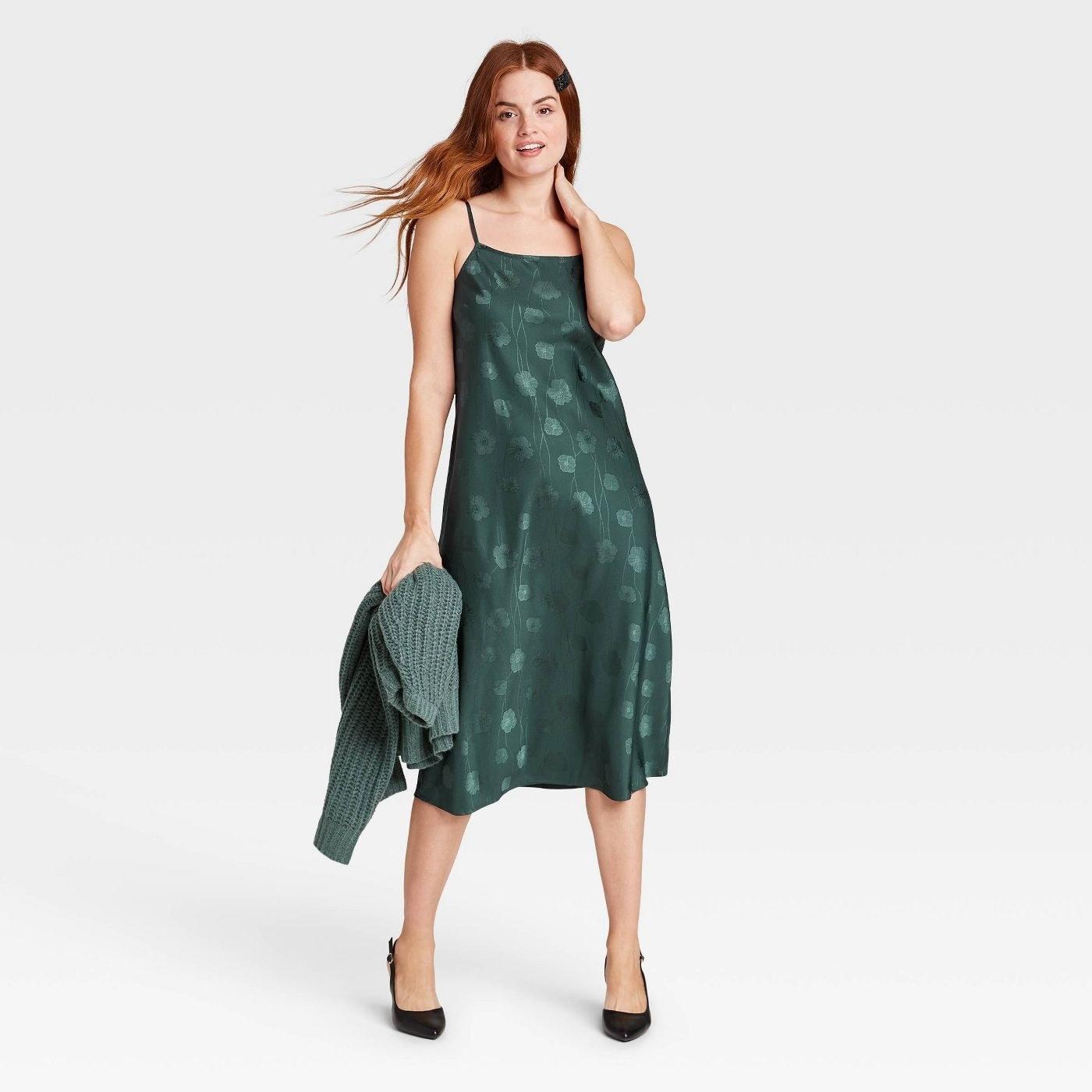 Model wearing  green slip dress
