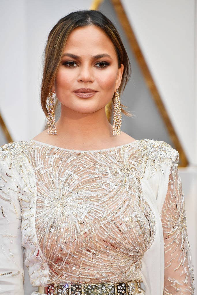 Chrissy wearing a sequined gown and her hair up on a red carpet