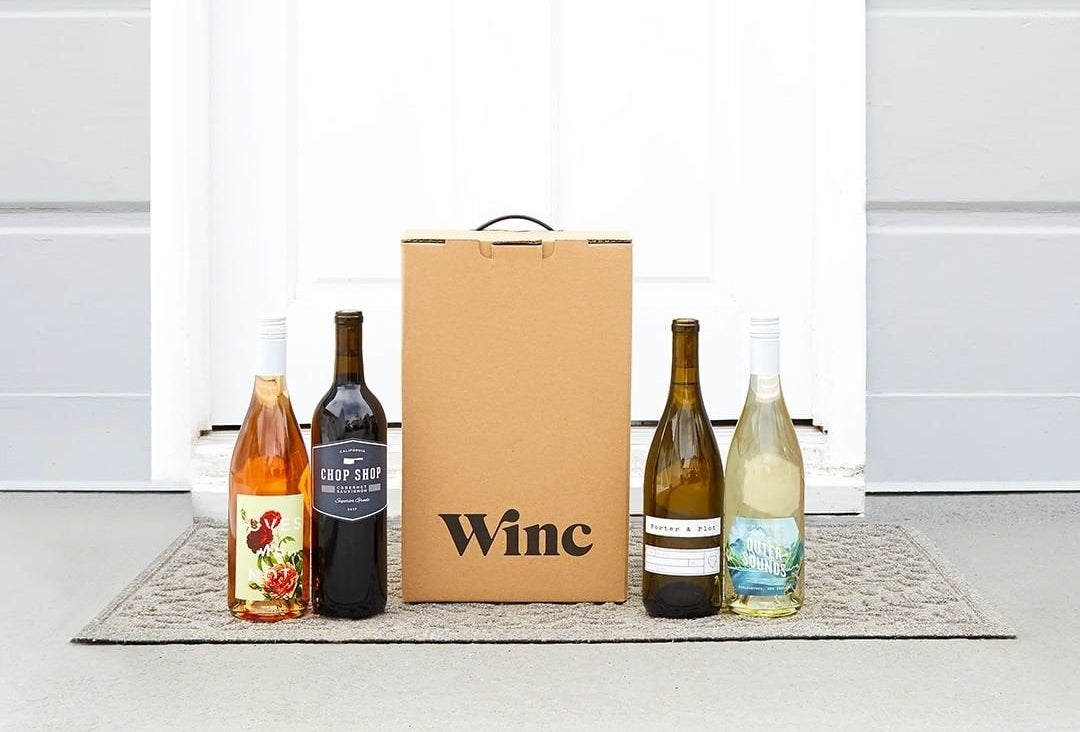 """A cardboard box on a doorstep that says """"Winc"""" next to four bottles of wine"""