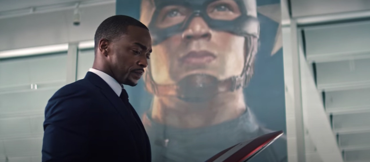 Mackie looks at Captain America's shield in front of a Captain America banner in The Falcon and the Winter Soldier