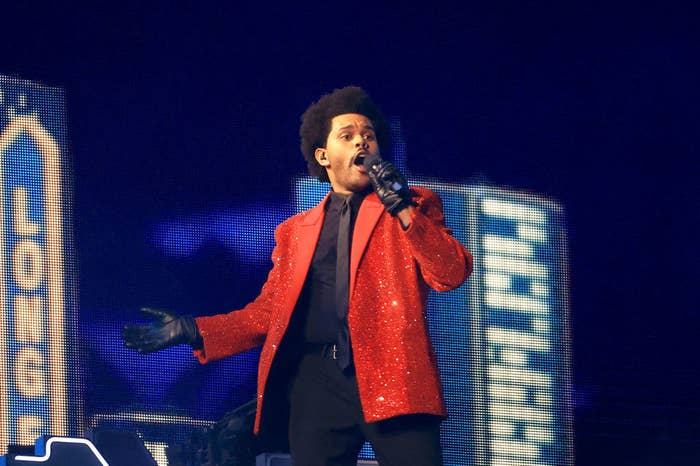 The Weeknd singing while wearing a dress shirt, tie, slacks, a sequined jacket and leather gloves