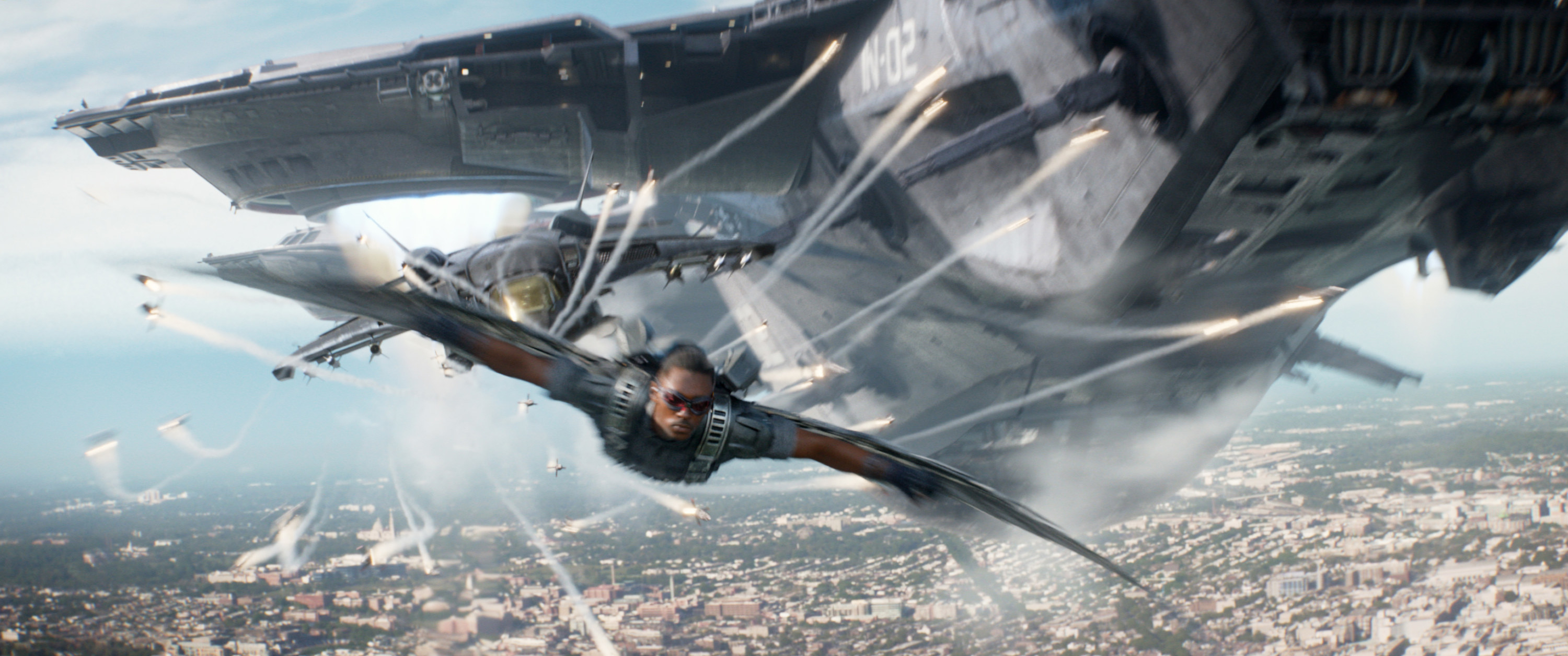 Mackie flies through the air underneath a plane as The Falcon in Captain America: The Winter Soldier