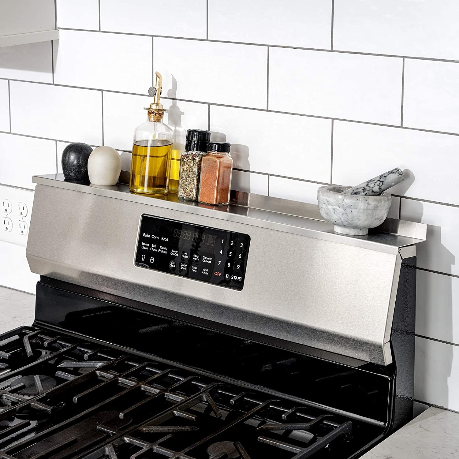 The stainless shelf on top of the back of a stove range holding oil, salt and pepper shakers, other spices, and a mortar and pestle