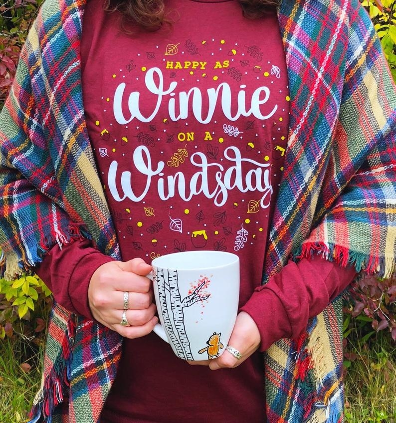 "model wearing red crewneck that says ""happy as winnie on a windsday"""