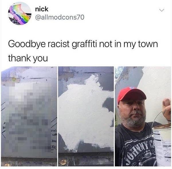 man painting over racist graffiti