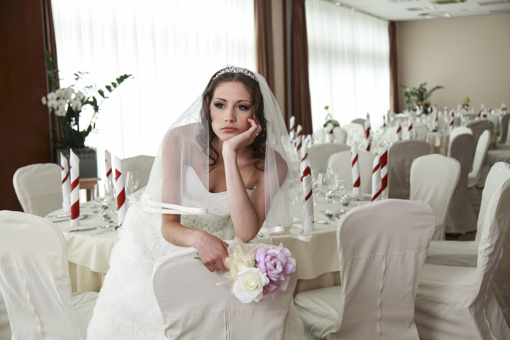 A disappointed bride sits alone at her wedding