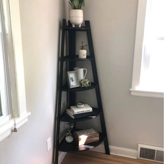 black corner bookcase with books and decorative items on it