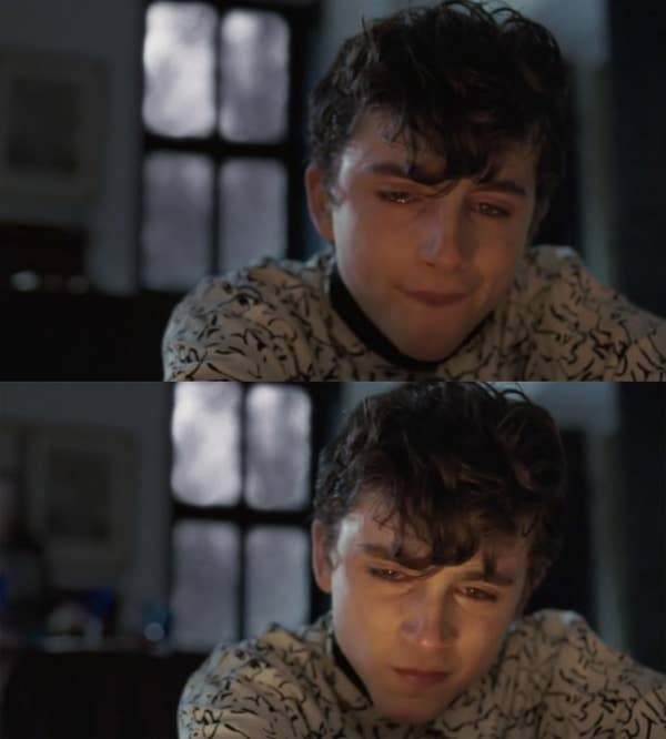 Elio sitting in front of a fireplace and silently crying.