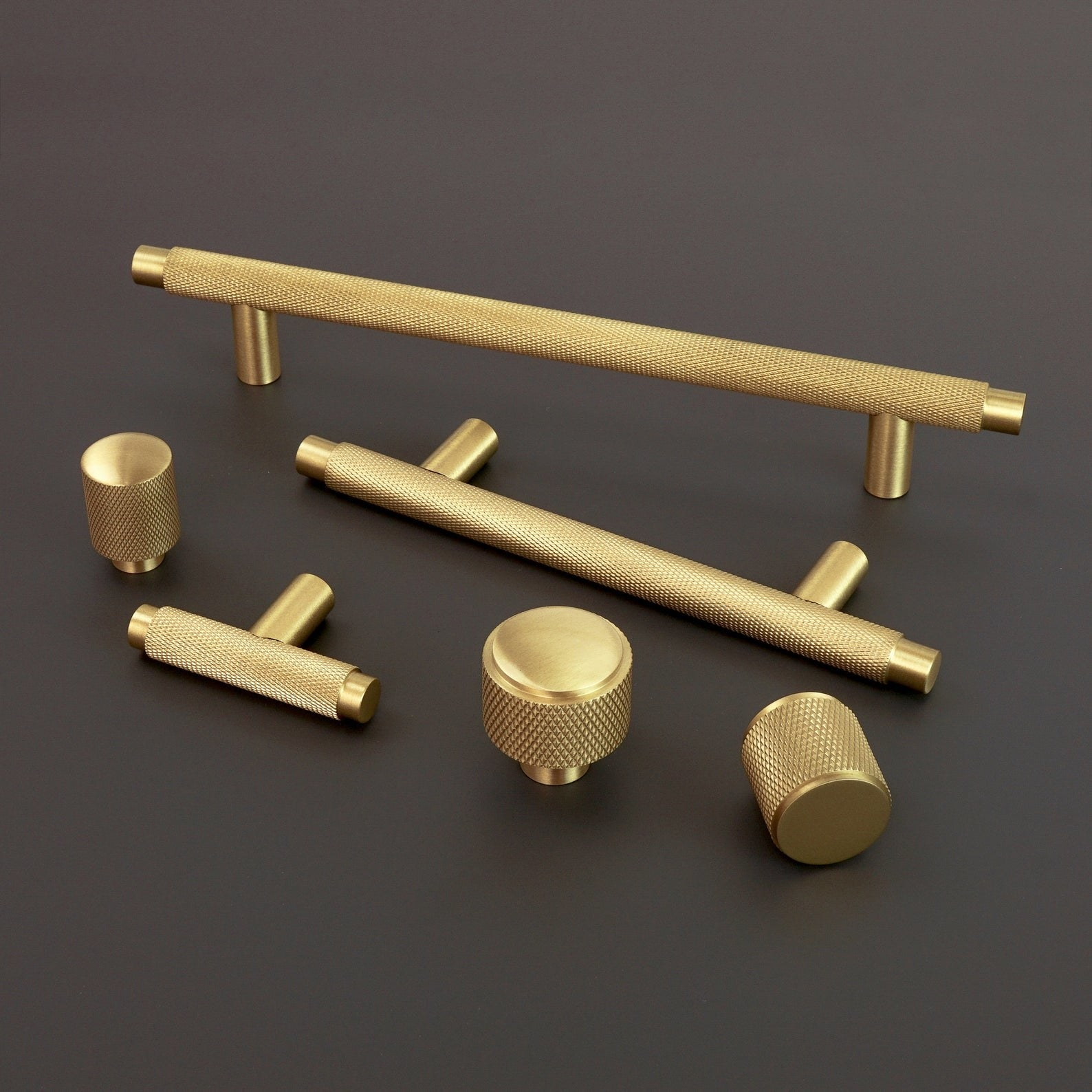 three knurled solid brass pulls and three knurled solid brass knobs on a black surface