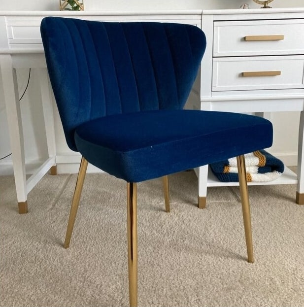 blue accent chair with gold legs and a tufted back