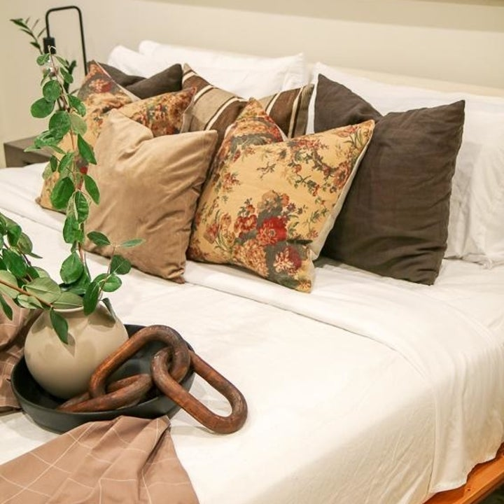 Floral-printed pillow next to solid green and beige pillows on a bed