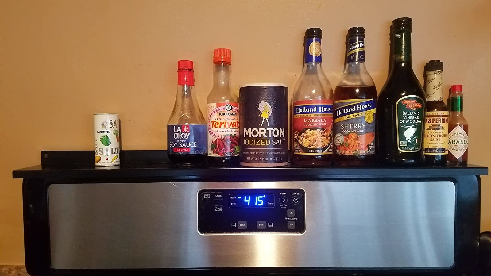 A reviewer's photo of the black shelf holding various pantry items like soy sauce and tabasco