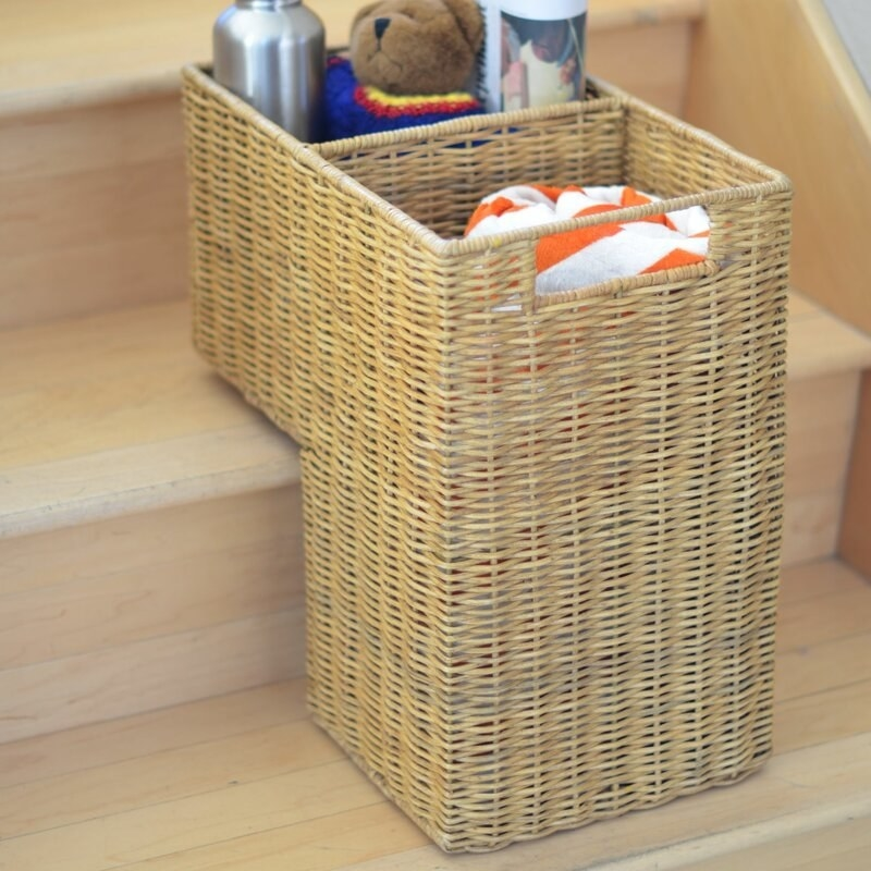 The wicker basket holding a towel, water bottle, and teddy bear