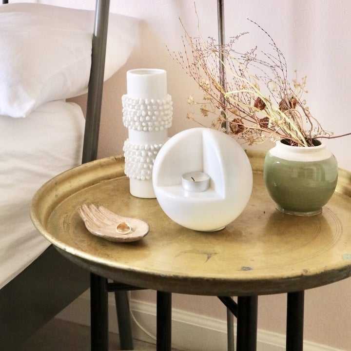 circle-shaped candle holder on nightstand with dried flowers