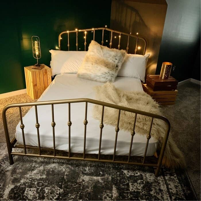 gold bed frame in a room with lights all around it