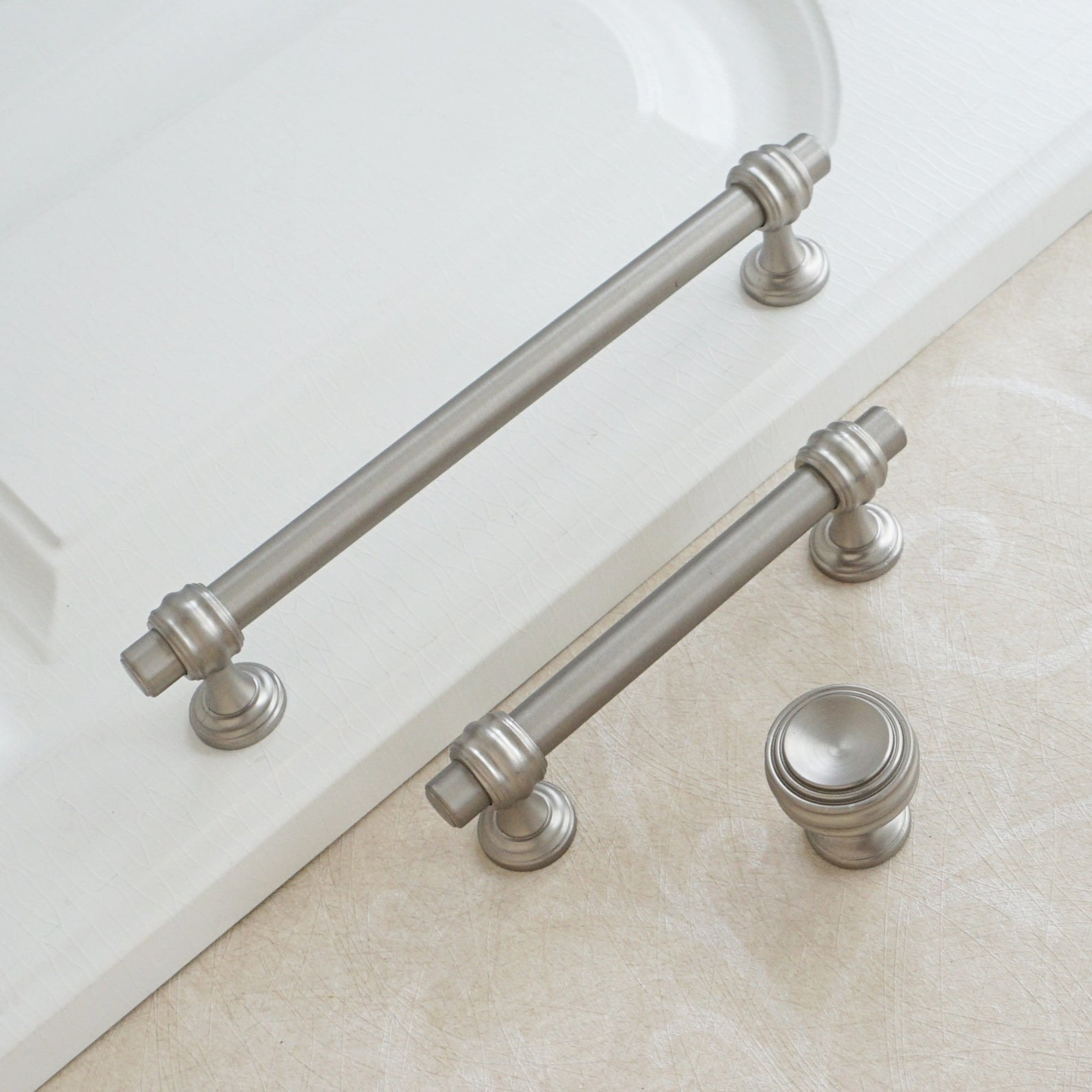 two brushed nickel pulls and one brushed nickel knob