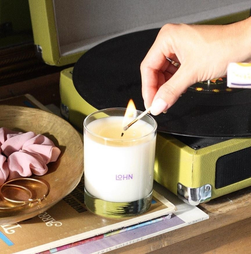 A person lighting a candle with a match
