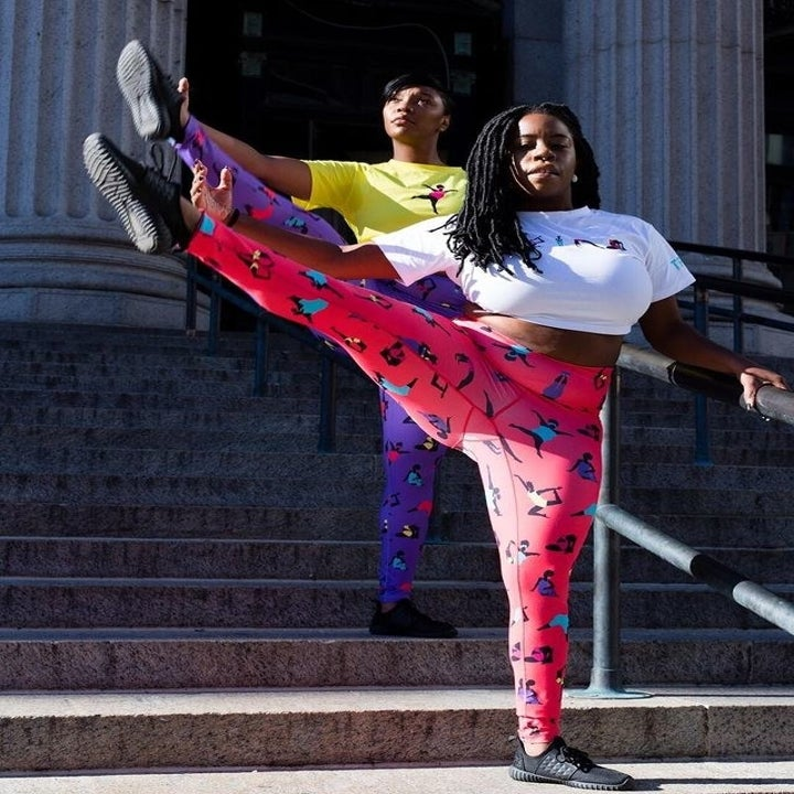 Two dancers with their leg held high wearing the pink and purple pairs of leggings