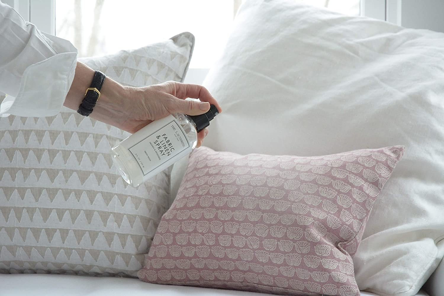 A person using the fabric spray onto a set of cushions