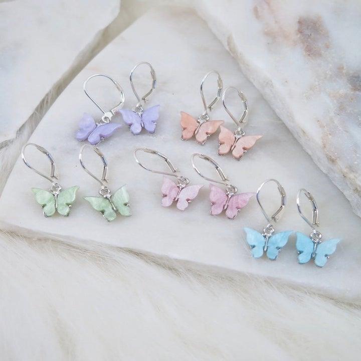 pastel mini butterfly dangling earrings on a marble table