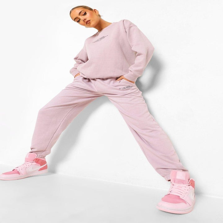 model in matching top and bottom light pink acid wash sweatshirt and joggers
