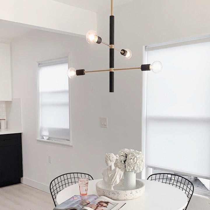 black and gold cross chandelier with four lights