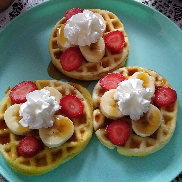 Three waffles made with the griddle with strawberries and bananas on top