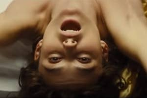 Anna lying upside down with her mouth open in Anna Karenina