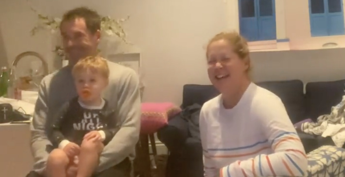 Amy Schumer laughs with her husband and son while watching the Super Bowl