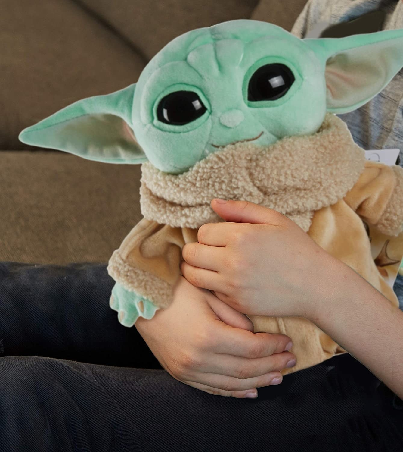 A hand holding A Baby Yoda plushie