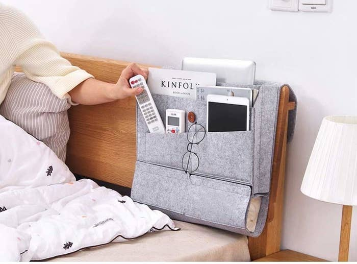 A person in bed putting a remote in a bedside caddy that's attached to the headrest
