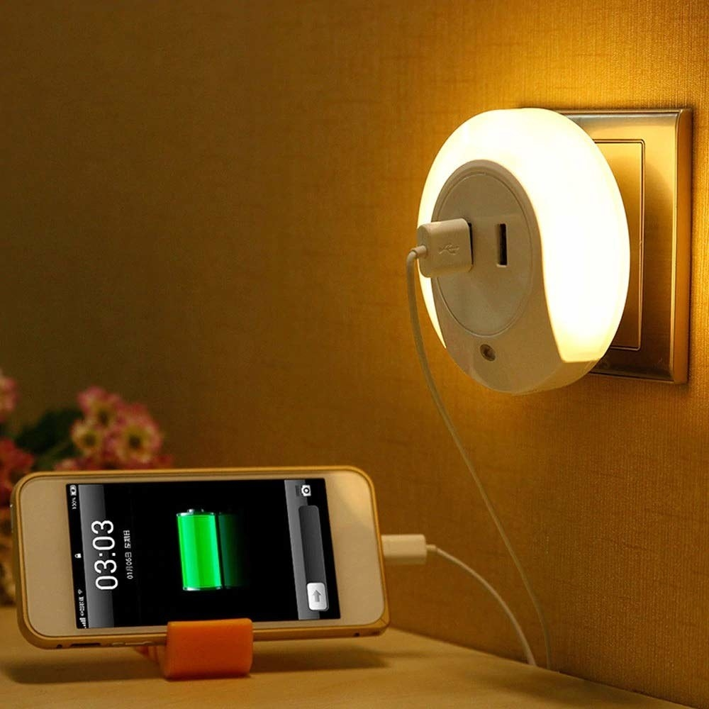 A night lamp attached to a wall socket while charging a smartphone off one of its USB sockets