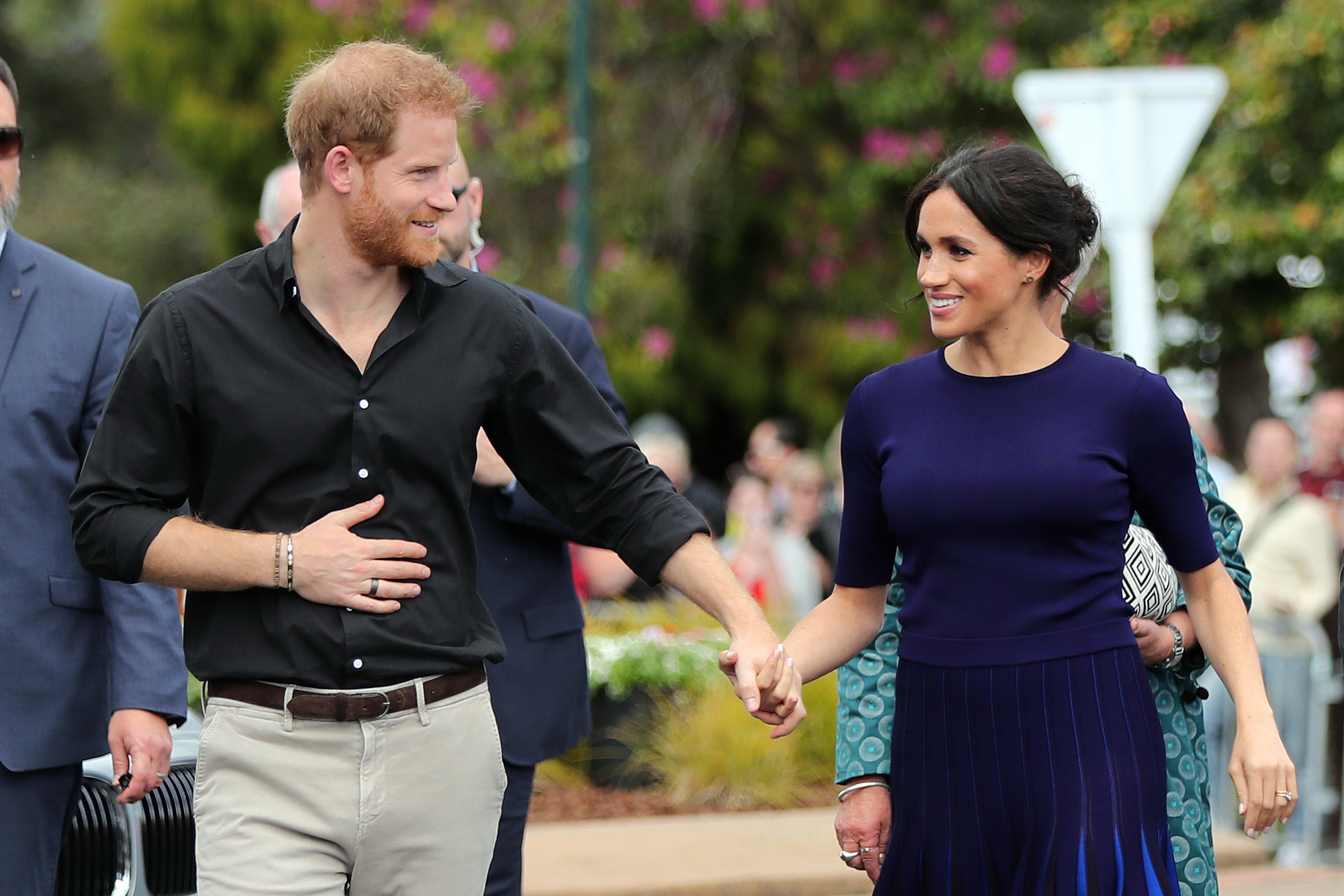 Harry and Meghan hold hands while on a walk