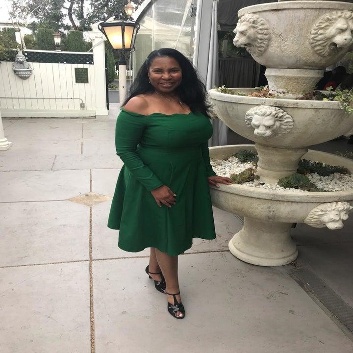 reviewer wearing dress in green