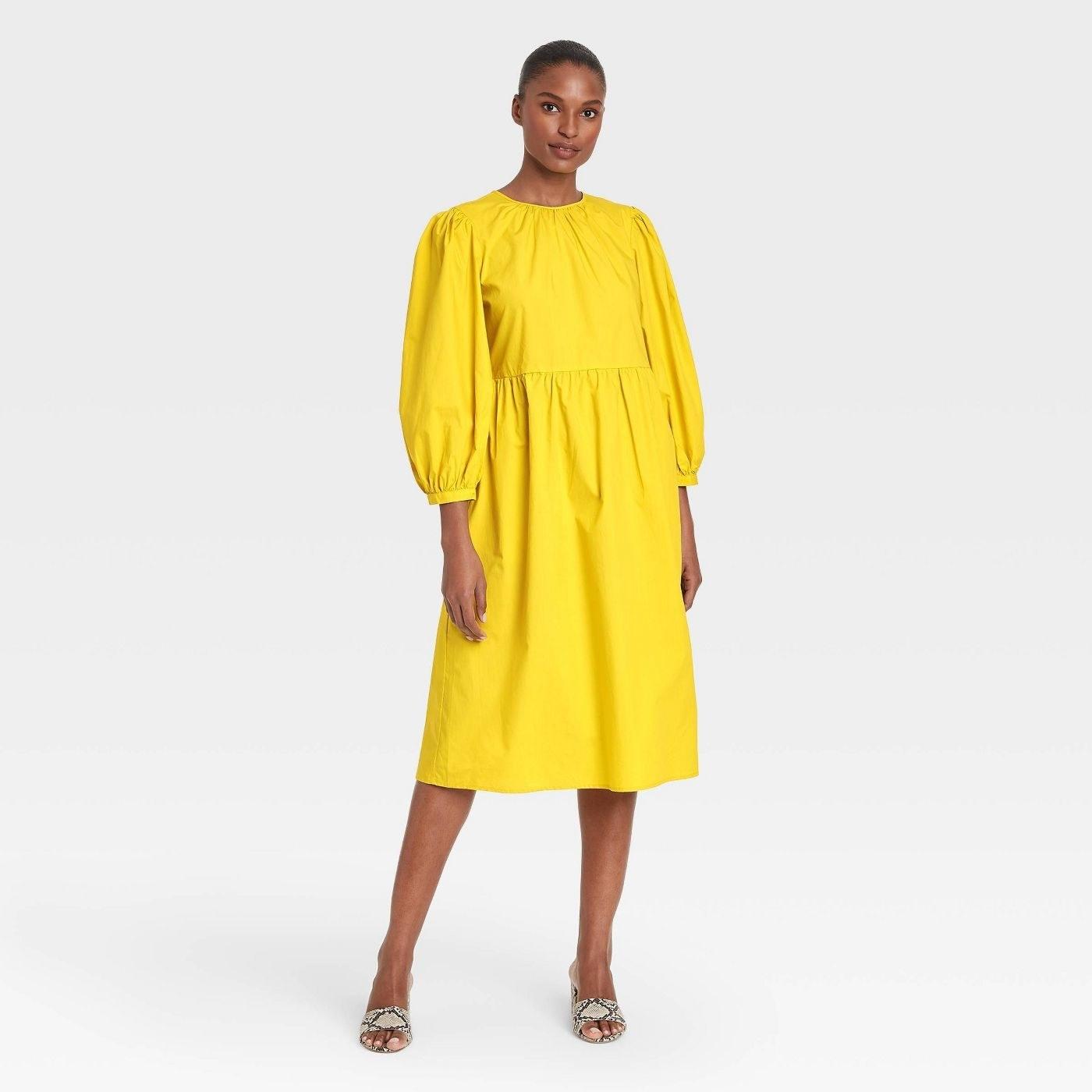 Model wearing bright yellow midi dress