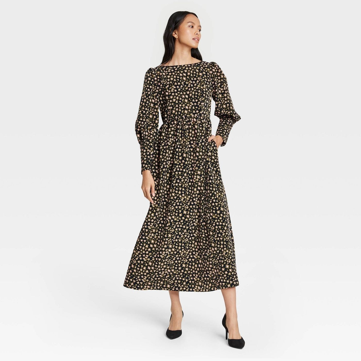 Model wearing black dress with a yellow dotted pattern