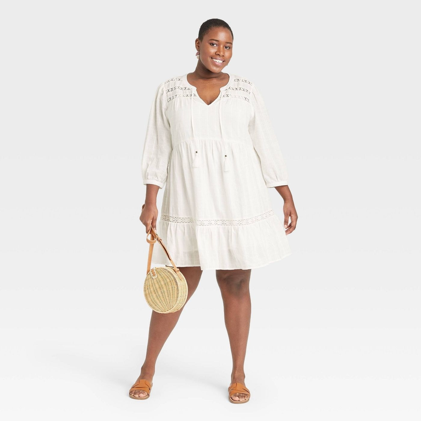 Model wearing white dress with tassels