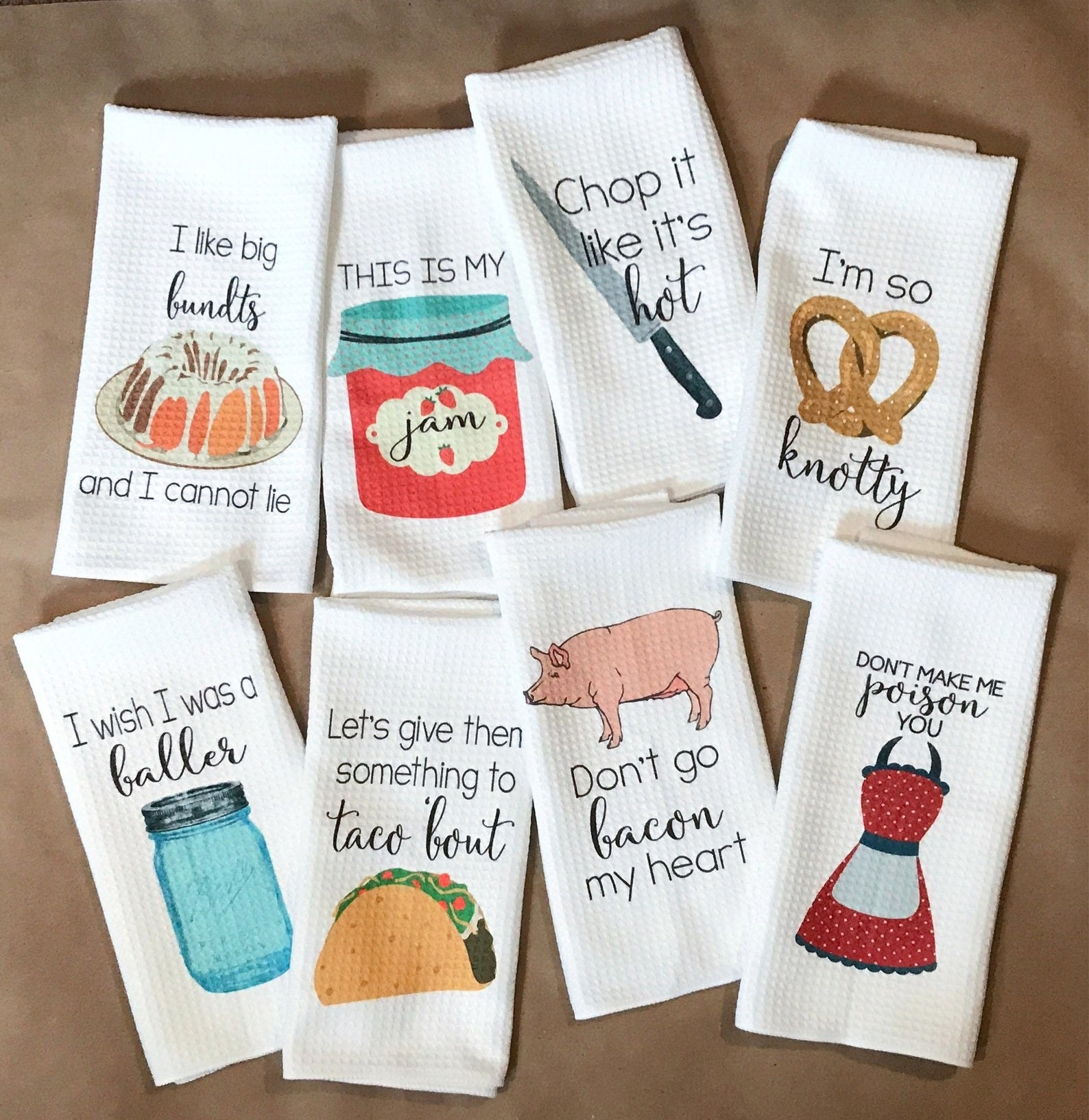 "eight kitchen towels that are white wiht one colorful item on it and a quote. ONe says ""Let's give them something to taco 'bout"" with a taco underneath"