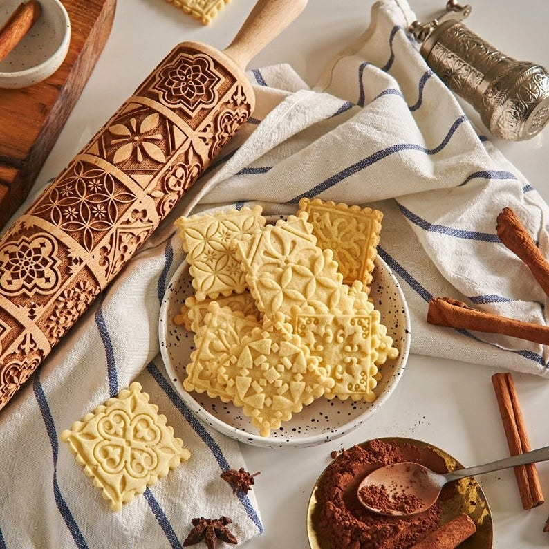 the wooden rolling pin with embossment designs engraved in it to impress upon the cookies and cookies in a bowl with designs on them from the pin