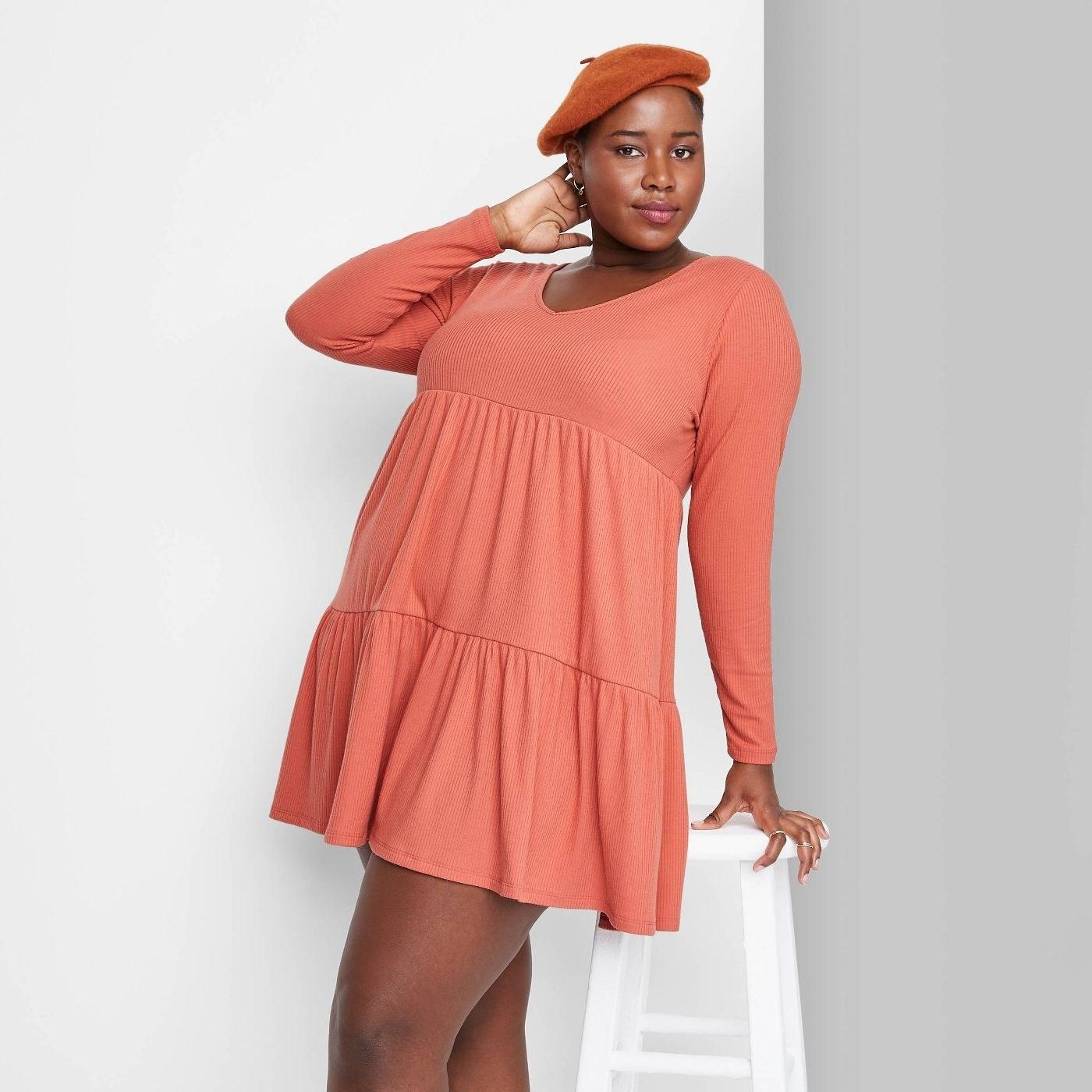 Model wearing ruffled orange dress