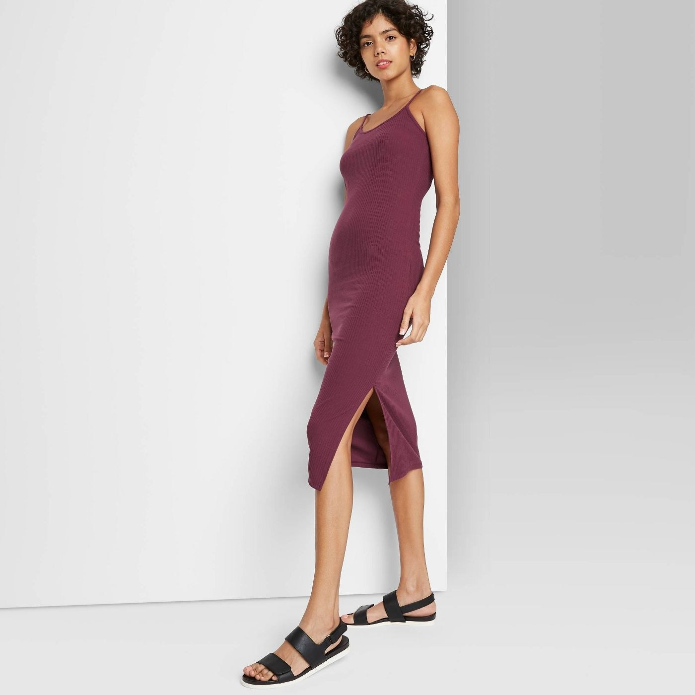 Model wearing  purple spaghetti strap dress with side slit