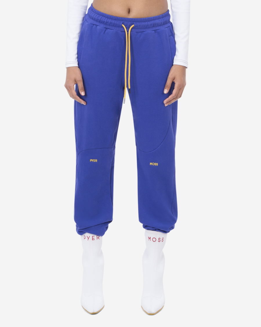 "Model wearing purple-y blue sweats with yellow drawstring and embroidery at the knees that reads ""Pyer Moss"""